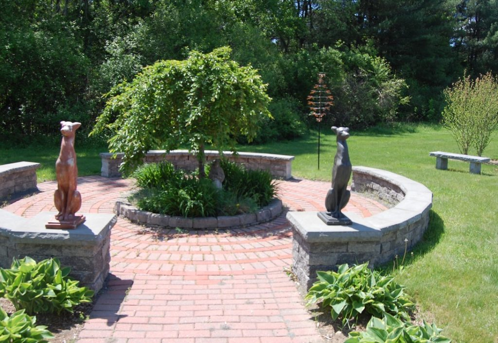 memorial garden with dedicated bricks, benches, greyhound statues and greenery
